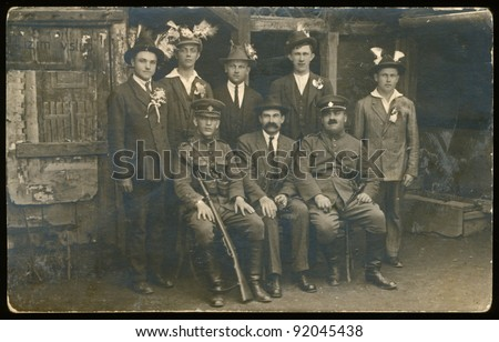soldiers and country men in front of wooden plank shanty - about 1945 - stock photo