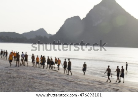 Soldiers are helping to clean the sand by the sea.Blur image
