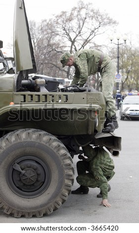 Soldiers drivers. The driver of the truck repairs. - stock photo
