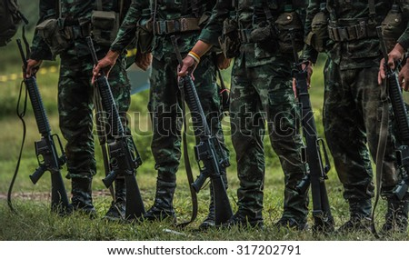 Soldiers , firing machine guns , in the sandbag bunker in the forest meadow green landscape .  - stock photo