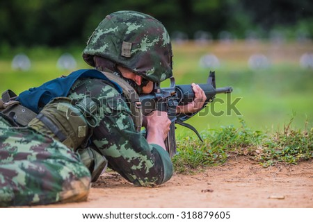 Soldiers , firing machine guns , in the sandbag bunker in the forest meadow green landscape  , (AARM 2015)