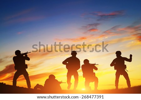 Soldiers in assault shooting with weapon, rifle at sunset. War, army, military. - stock photo