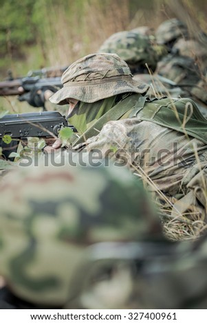 Soldiers in camouflage uniform training in the forest - stock photo
