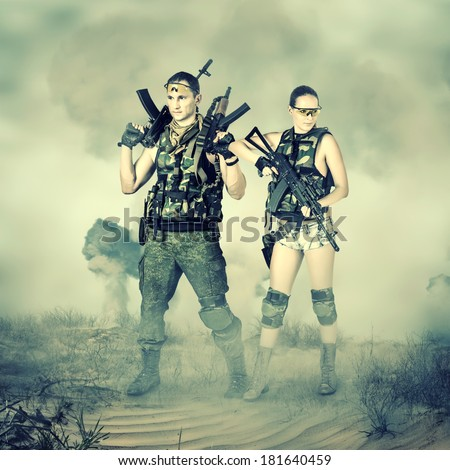 soldiers in full gear. Military man and woman with automatics for strikeball - stock photo