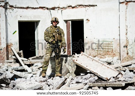 soldiers in full gear with weapons posing on rest - stock photo