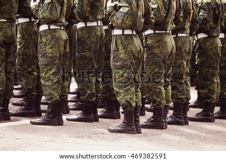 Soldiers in green uniforms stand at attention