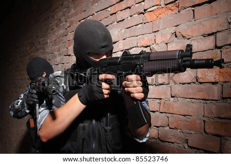 Soldiers or terrorists in black masks and heavy ammunition with automatic rifles - stock photo