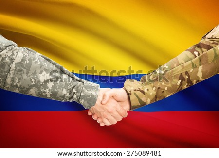 Soldiers shaking hands with flag on background - Colombia - stock photo