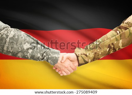 Soldiers shaking hands with flag on background - Germany - stock photo