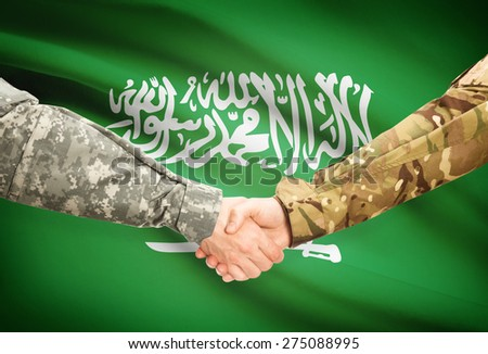 Soldiers shaking hands with flag on background - Saudi Arabia - stock photo