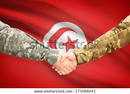 Soldiers shaking hands with flag on background - Tunisia - stock photo