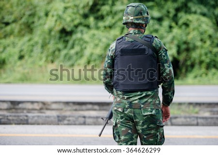 Soldiers stand back with blurred forest background. - stock photo