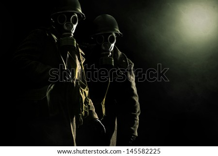Soldiers with gas mask in a dark background - stock photo