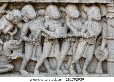 Soldiers with weapon carved on the historical wall of hindu temple, India - stock photo