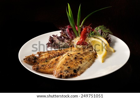 Sole fish with slice of lemon, lobster and garnish on a dish - stock photo