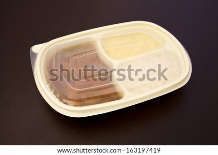 Sole with creole sauce and mashed potatoes in a closed package to go or to freeze. Package on brown leather background. - stock photo