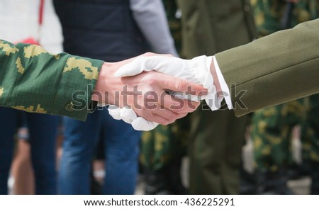 Solemn handshake of men in military clothes