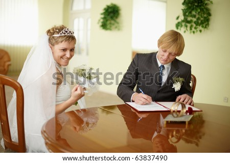 Solemn registration - the wedding ceremony. The bride and groom at the table - stock photo
