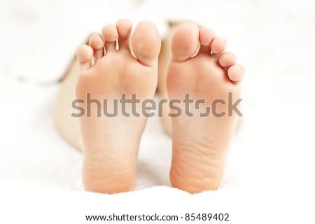 Soles of soft female bare feet in closeup - stock photo