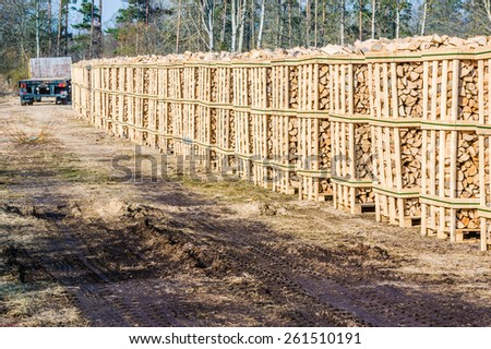 Solid biofuel as fire wood made of birch, stacked on pallets in outdoor stock. Dirt road in foreground and trailer at the end of stacks.