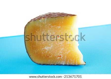 solid cheddar cheese on blue plastic plate - stock photo