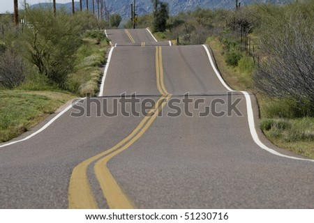 Solid double yellow lines accentuate the bumpy path as this paved road disappears into the distance in the early morning sun. - stock photo