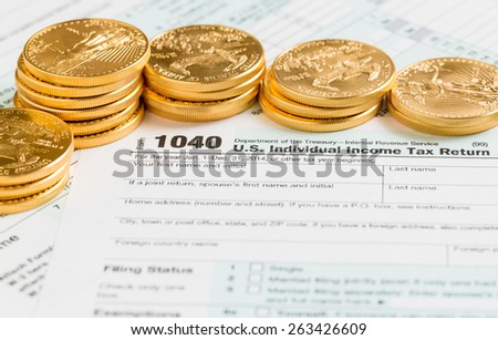 Solid gold eagle coins on USA tax form 1040 for year 2014  illustrating payment of taxes on forms for the IRS