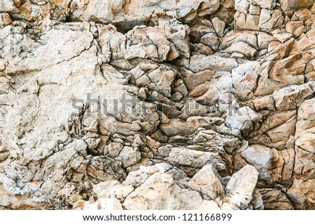 Solid limestone rock texture with muliple cracks, taken near the beach on a sunny day - stock photo