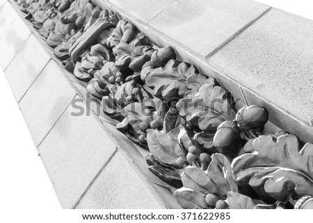 Solid oak leaves and acorns carved into an exterior stone column in a public park. Black and white image with copy space - stock photo