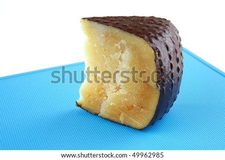 solid parmesan cheese on blue plastic board - stock photo