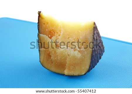 solid parmesan cheese on blue plastic board
