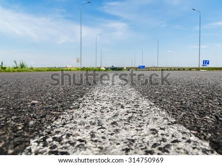 solid white line on asphalt road closeup. soft focus - stock photo