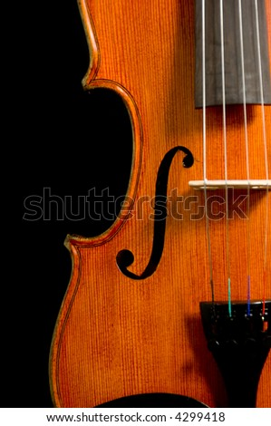 Solid wood violin or fiddle on black background
