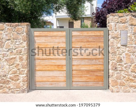 Solid wooden gates protecting a house. - stock photo