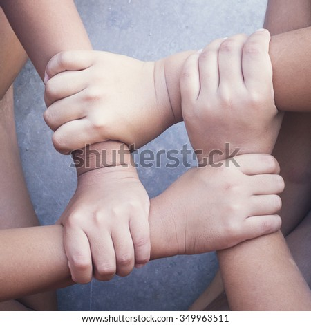 Solidarity concept using joined children hands. International Human Solidarity Day Communication Diversity Relationships Fellowship CSR Friendly Workgroup Collaboration Global Youth Service concept. - stock photo