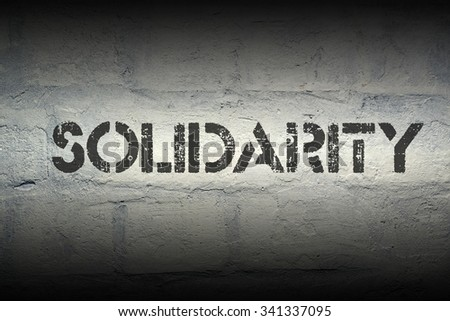 solidarity stencil print on the grunge white brick wall