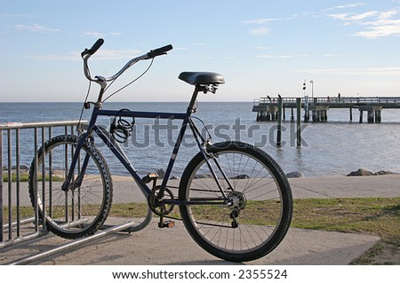 Solitary bike captured against backdrop of beach and pier - stock photo