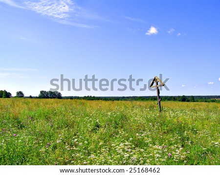 solitary cross on yellow autumn field