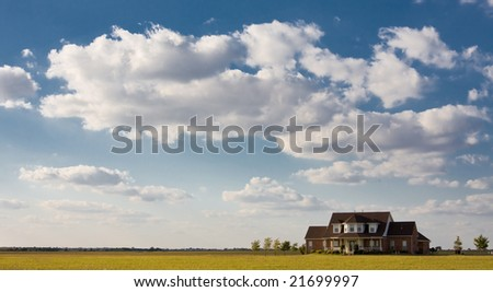 Solitary lonely  house sits by itself on large field with blue sky and clouds. - stock photo