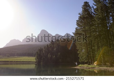Solitary man fishing in tranquil lake on camping trip, mountain valley bathed in sunlight (lens flare) - stock photo