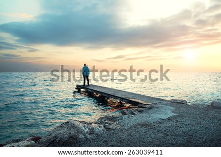 Solitary man stand on boardwalk observing the sea - stock photo
