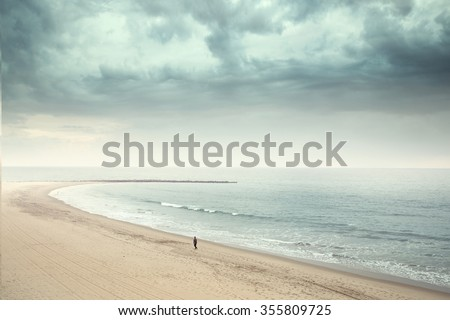 Solitary man walking on the wide beach  - stock photo