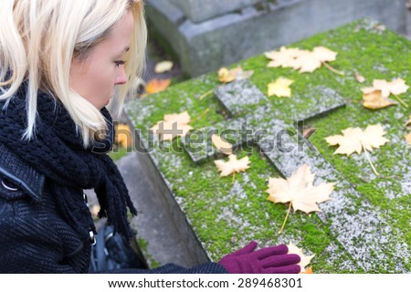 Solitary woman mourning with her hand on headstone, remembering dead relatives in on Pere Lachaise cemetery in Paris, France. - stock photo