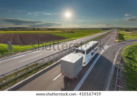Solitude bus driving in blurred motion on the freeway at beautiful sunny day. Transport and travel scene on the motorway towards the sun near Belgrade, Serbia. - stock photo