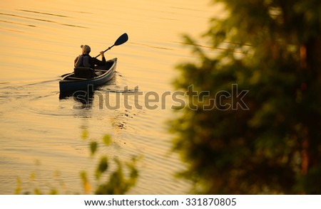 solitude concept with man alone in a lake during a sunrise or sunset in deep contemplation - stock photo