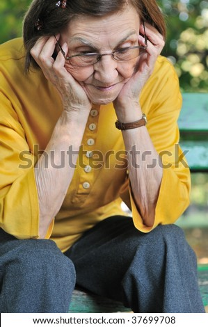 Solitude - portrait of worried senior woman - stock photo