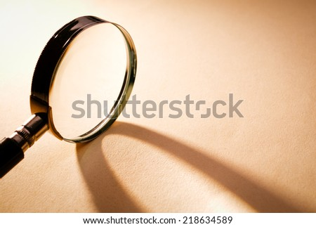 Solo Close up Magnifying Glass on Light Brown Platform - stock photo