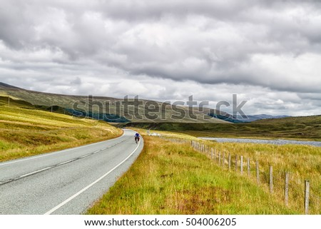 Solo female cyclist cycle through Scottish mountains with her bicycle fully loaded with equipment and camping gear.