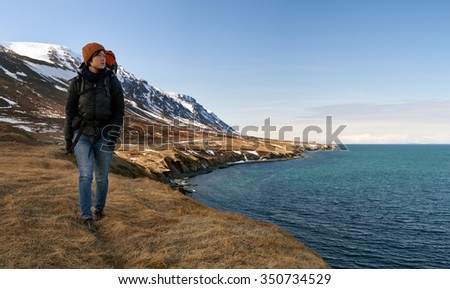 Solo independent asian woman traveler on active holiday, hiking trekking in beautiful natural outdoor landscape by the ocean and mountains