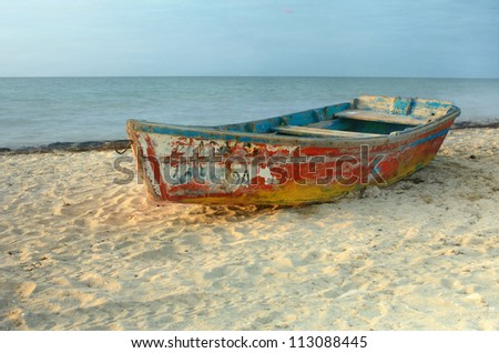 Solo rowboat with peeling paint resting on sandy beach in Progreso, Yucatan, Mexico - stock photo